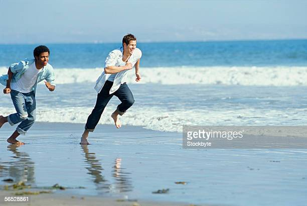 two young men running on the beach