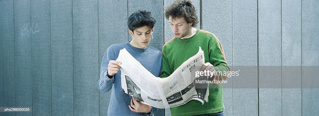 Two young men sharing newspaper : Stockfoto