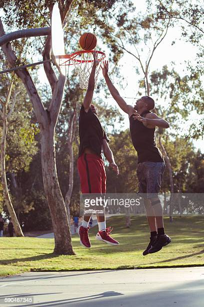 Two young men shooting basketball hoops in the park at sunset