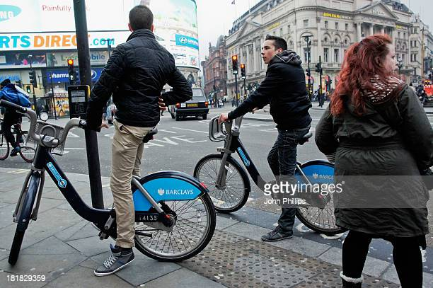 CONTENT] Two young men sit astride hired bikes at the side of the road in London's Piccadilly Circus A young woman with dyed red hair looks across...