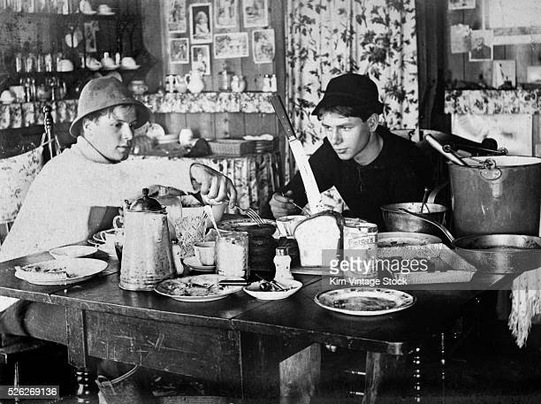 Two young men sit down to a big breakfast at the table