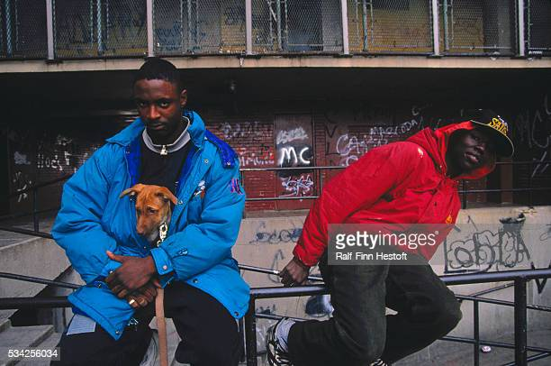 Two young men sit on a railing outside the CabriniGreen housing project in Chicago One man holds his pet dog inside his jacket to keep it warm