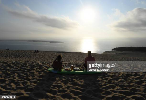 Two young men sit on a surf board eating dinner on top of the Dune Du Pilat as the sun begins to set on the longest day in the Northern Hemisphere on...