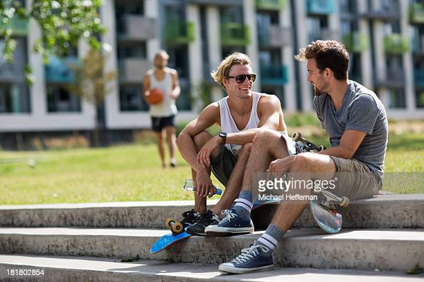 two young men sitting chatting in a park