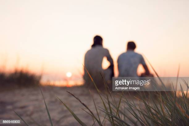 two young men sitting on beach at sunset - only young men stock pictures, royalty-free photos & images