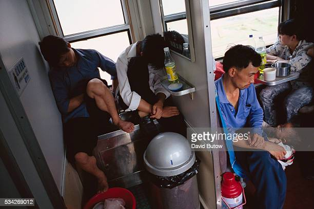 Two young men sleep in a cramped wash area of a crowded train during a trip through the Sichuan province of China