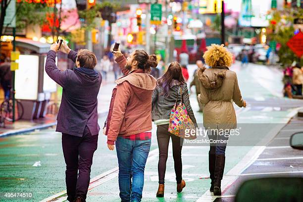 two young men snapping pictures with mobile phones on broadway - broadway manhattan stock photos and pictures