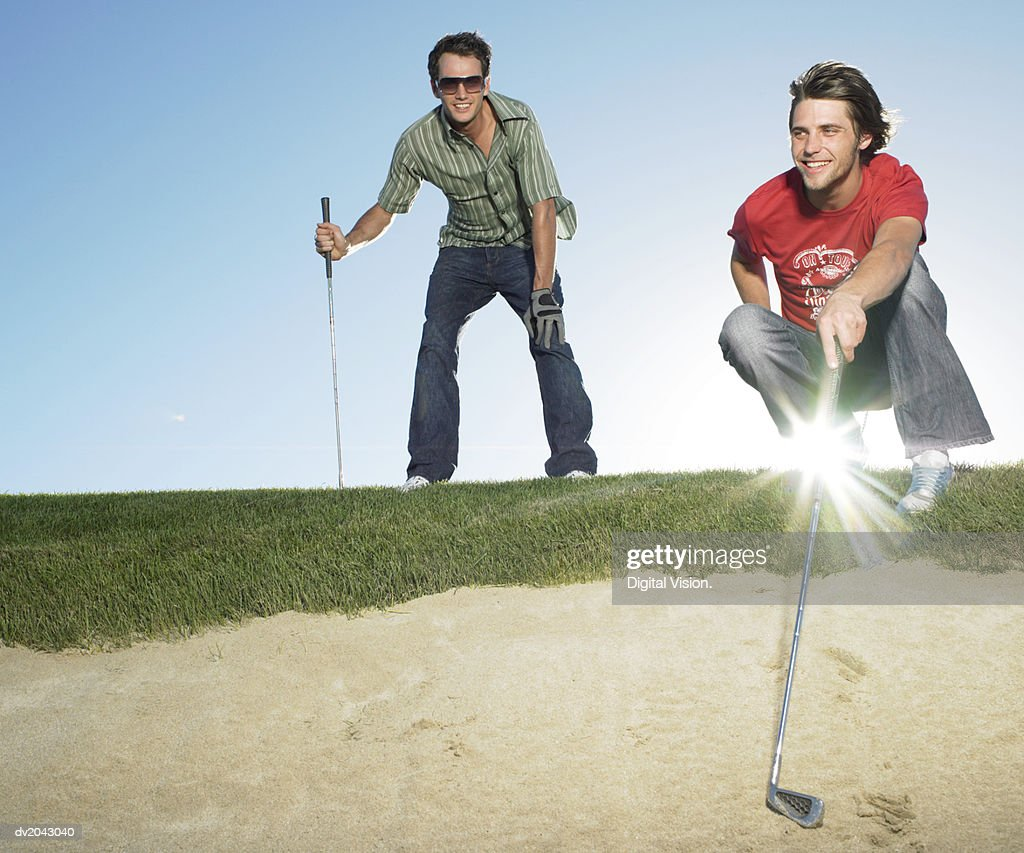 Two Young Men Standing at the Edge of a Sand Bunker Holding Golf Clubs : Stock Photo