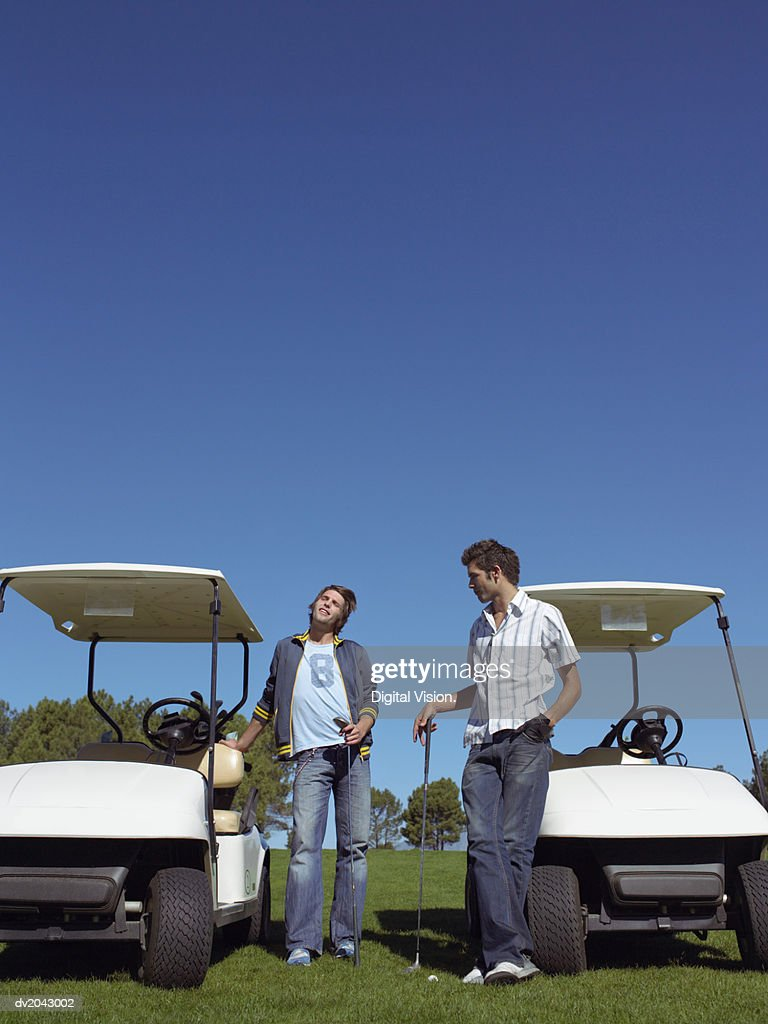 Two Young Men Standing by Golf Buggies and Holding Golf Clubs : Stock Photo