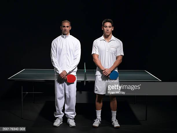 Two young men standing on opposite sides of table tennis net, portrait