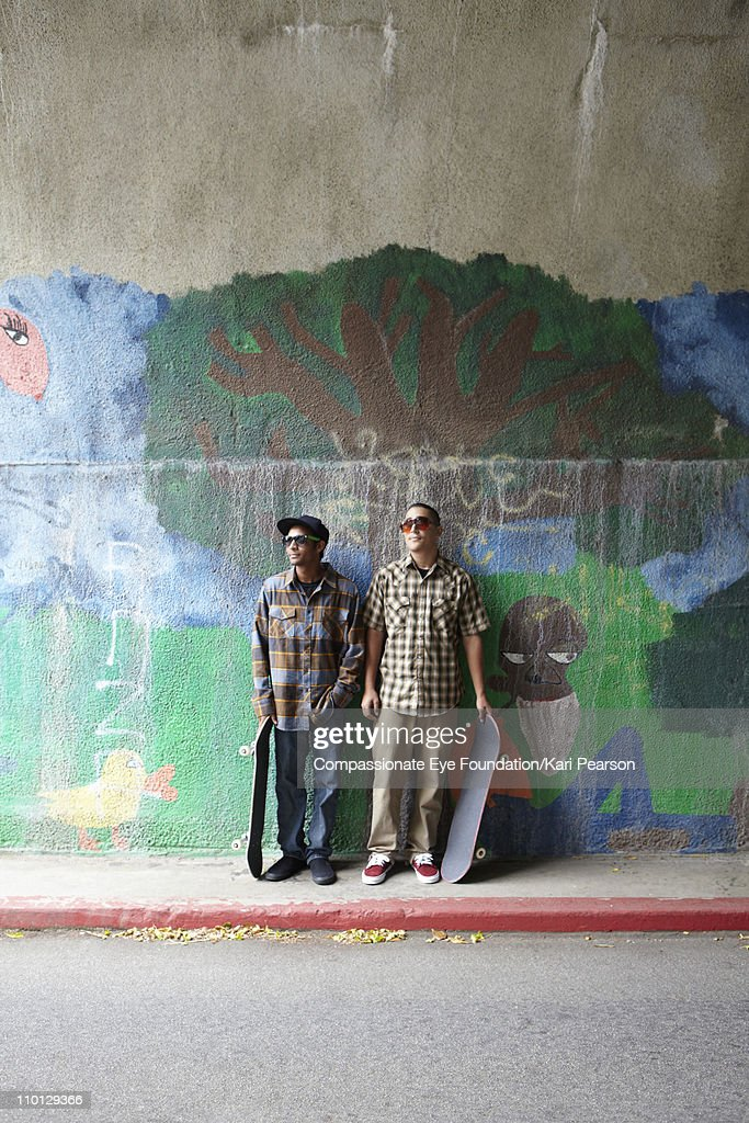 Two young men standing with skateboards : Stock Photo
