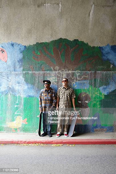 Two young men standing with skateboards