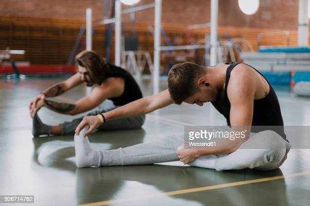 two young men stretching in gym - warming up stock pictures, royalty-free photos & images
