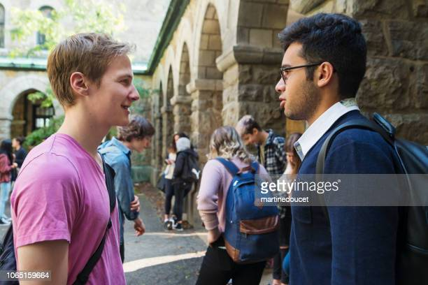 "two young men students chatting in college entrance. - ""martine doucet"" or martinedoucet stock pictures, royalty-free photos & images"