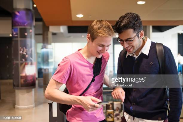 "twee jonge mannen studenten chatten in university college lobby. - ""martine doucet"" or martinedoucet stockfoto's en -beelden"