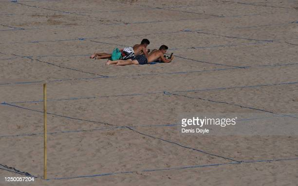 Two young men sunbathe in their designated ropedoff area on Poniente beach a day after the town's beaches were reopened after three months of closure...