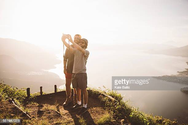 Two young men taking selfie at Lake Atitlan on digital camera, Guatemala