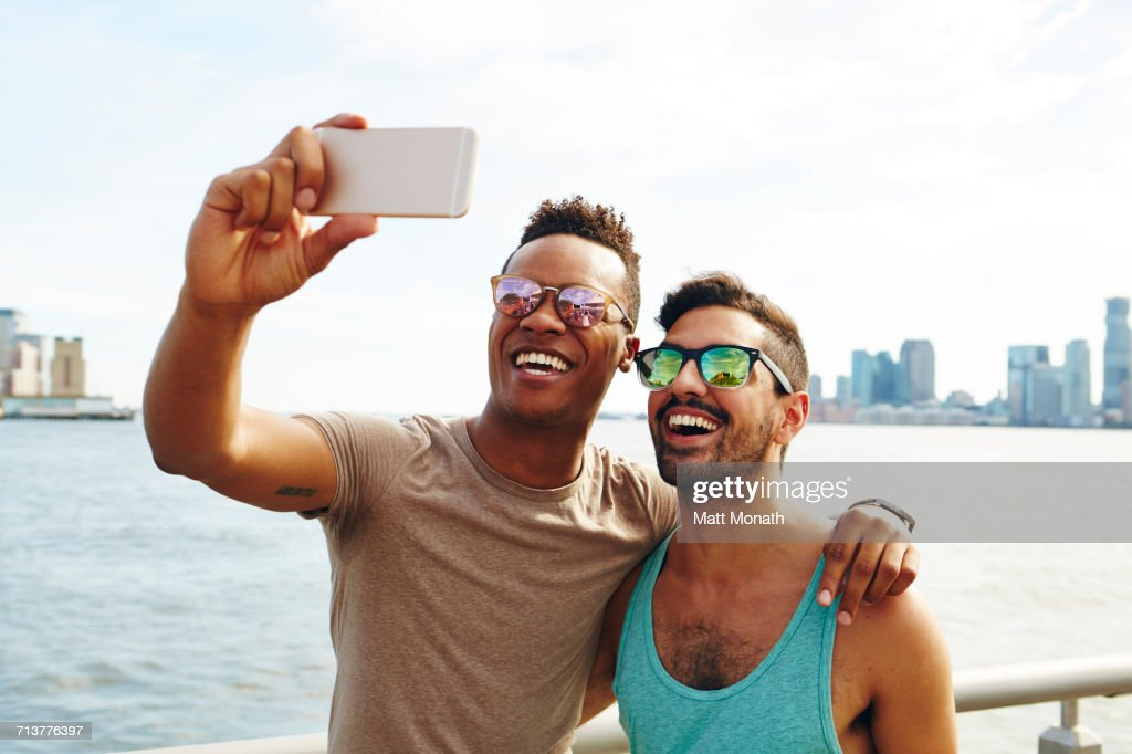 Two young men taking smartphone selfie on waterfront, New York, USA : Stock Photo