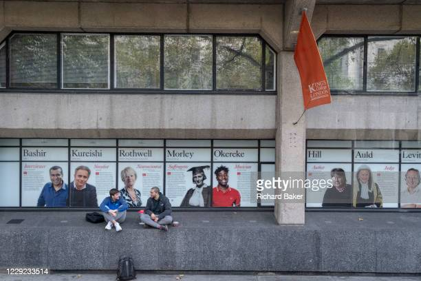 Two young men talk on a wall near the faces of past alumni a wall outside King's College London University on the Strand, during the second wave of...