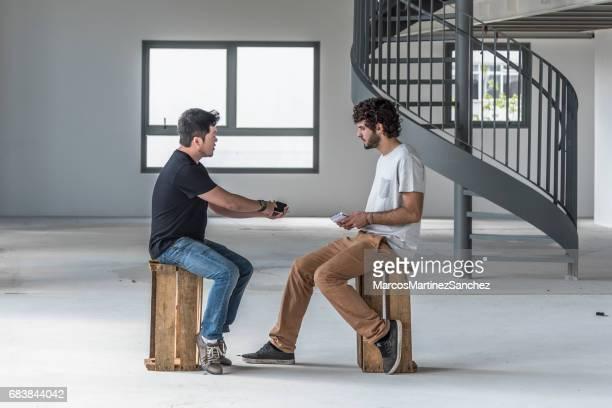 dois jovens falando em telefones celulares com um apontando para o dispositivo - debate - fotografias e filmes do acervo