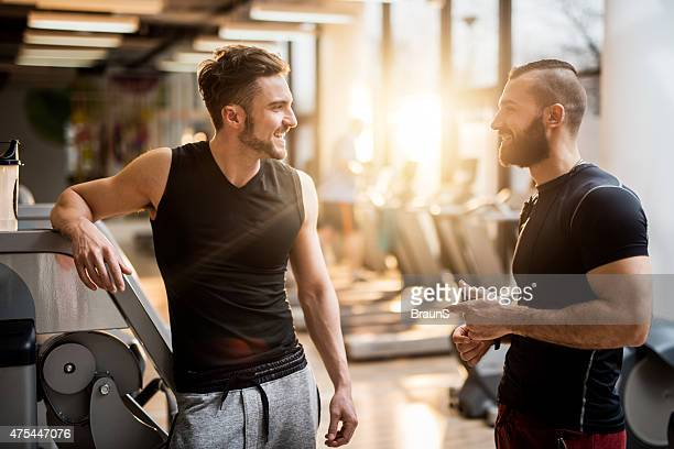 Two young men talking to each other in health club.