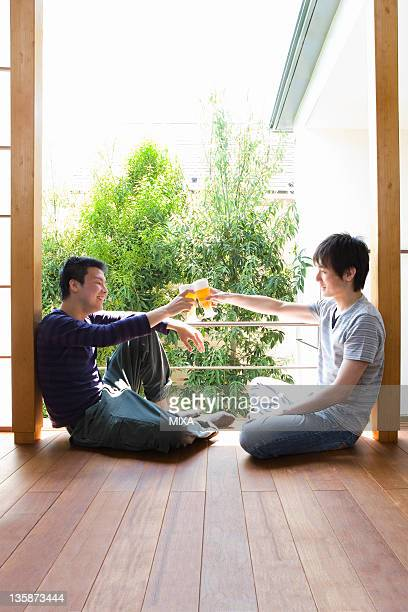 Two young men toasting by the window
