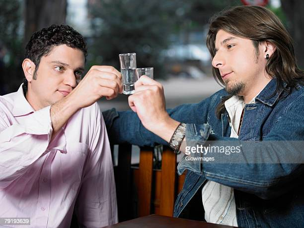 Two young men toasting with shot glasses of tequila
