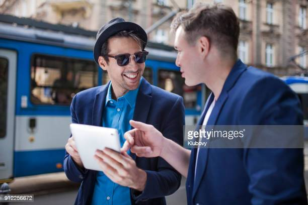 two young men using tablet - malopolskie province stock pictures, royalty-free photos & images