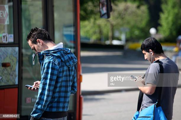 two young men waiting for the bus. - editorial stock pictures, royalty-free photos & images