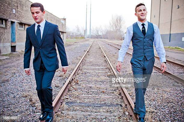 Two young men walking outside on train tracks.