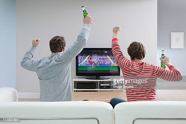 Two young men watching football on television