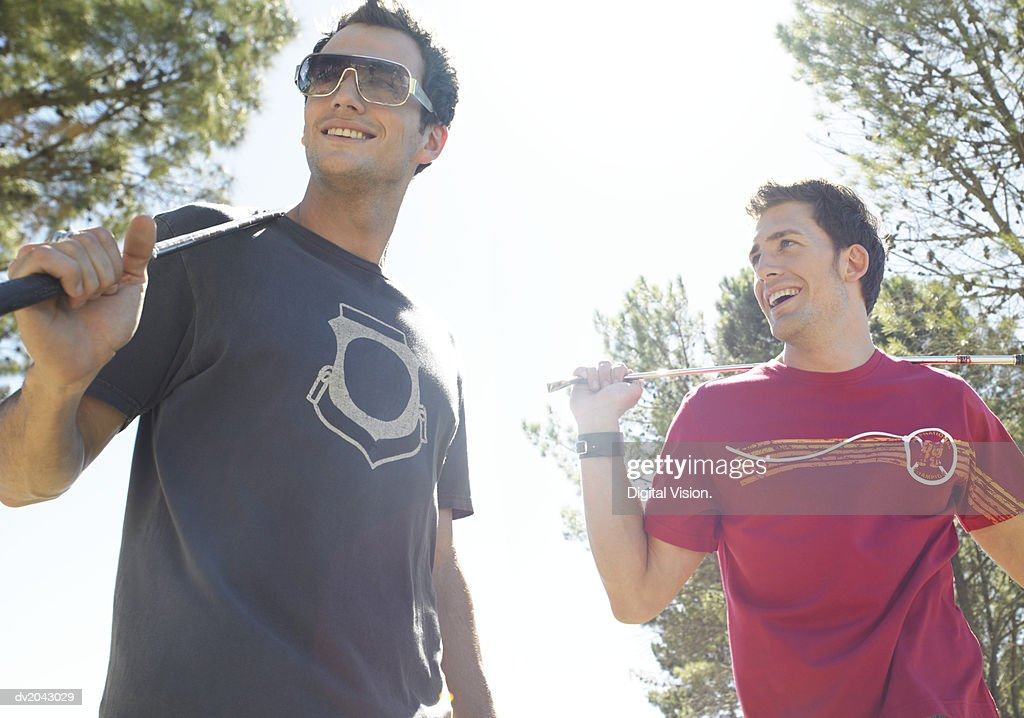 Two Young Men Wearing T Shirts and Holding Golf Clubs : Stock Photo