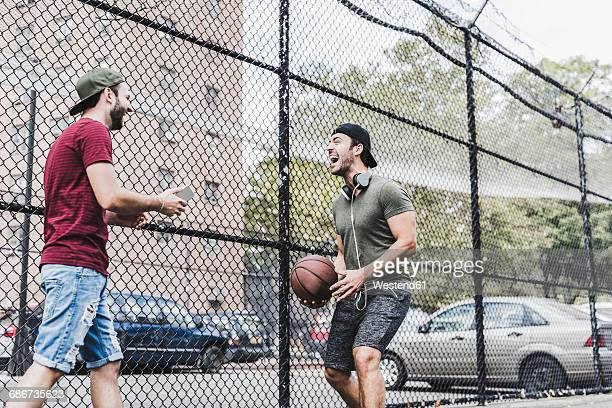 Two young men with basketball having fun on an outdoor court