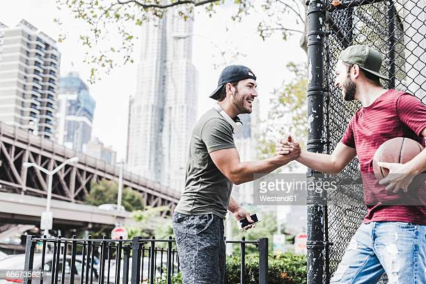 Two young men with basketball meeting outdoors