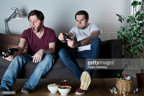 Two young men with excited and disgusted expressions playing Sony PlayStation 3 video games on a sofa taken on July 9 2013