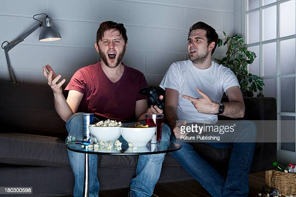 Two young men with frustrated expressions playing Sony PlayStation 3 video games on a sofa taken on July 9 2013