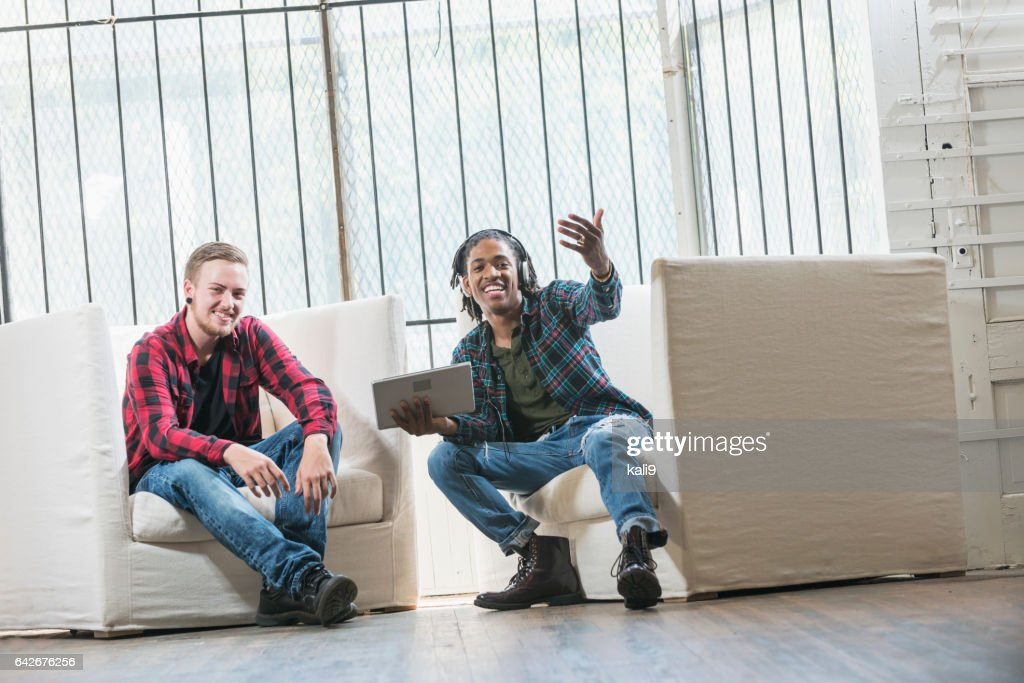 Two young men with tablet, waving someone to join them : Stock Photo