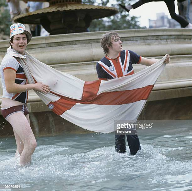 Two young men with Union Jack t-shirts and an England flag wade in the fountains at Trafalgar Square during the wedding celebrations of Charles,...