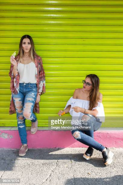 Two young Mexican women eating ice-cream