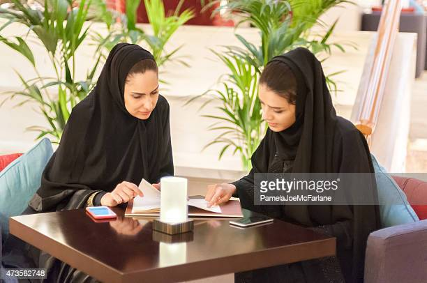 Two Young Middle Eastern Women Looking at Menu in Café