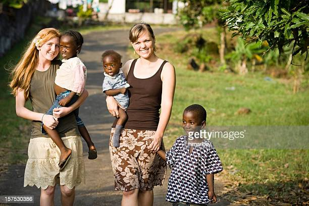 Two young missionaries with Liberian children
