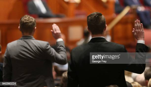 Two young Mormon priesthood members raise their hands to sustain President Russell M Nelson as the 17th President of the Mormon Church during the...