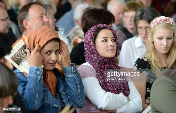 Two young mothers from Afgahistan who have been granted asylum in Germany attend a benefit concert in Troeglitz Germany 21 June 2015 The Leipzig...