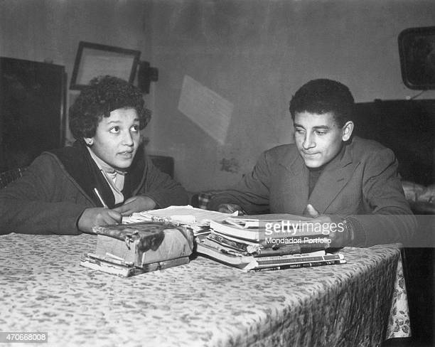 'Two young mulatto youths Emma and Giuseppe Lebrum study sitting at the table of the kitchen at their home where they live with their mother Giuseppe...