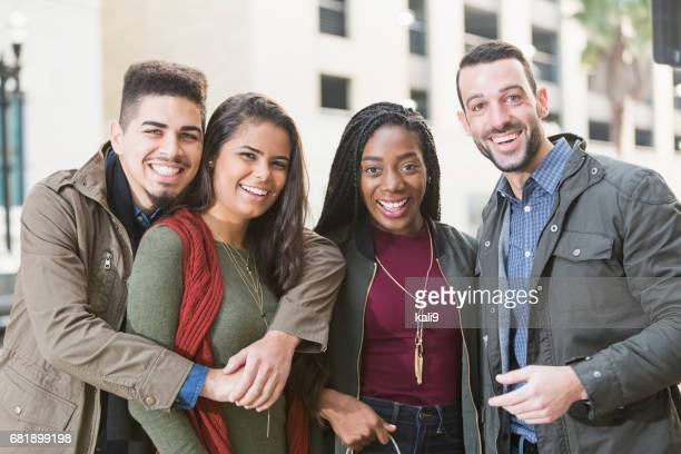 Two young multi-ethnic couples outside building