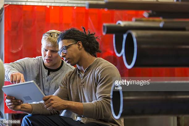 Two young multi-ethnic men using digital tablet
