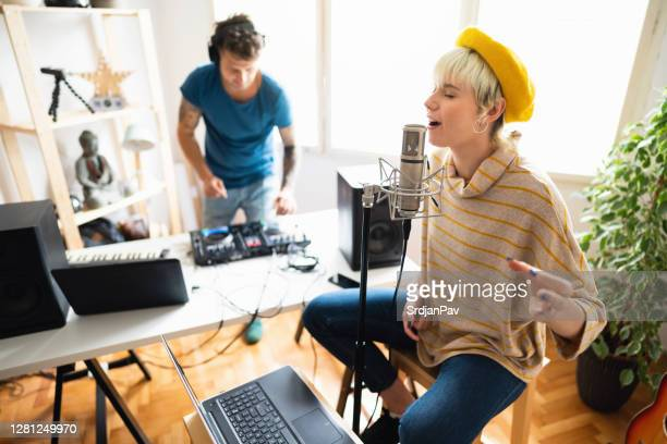 two young musicians recording vocals for their new song in the home music studio - producer stock pictures, royalty-free photos & images