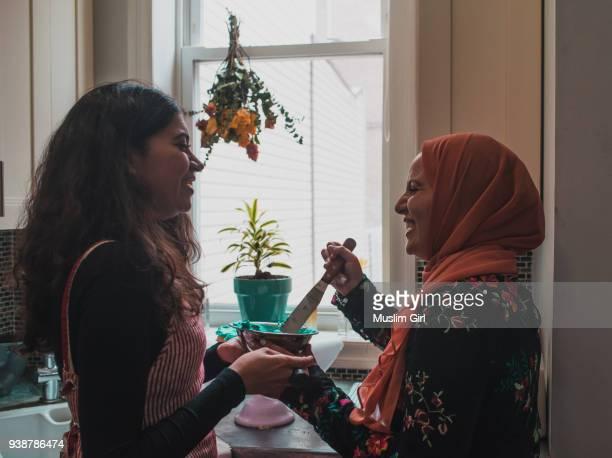 two young muslim women frosting the cake - cultura árabe fotografías e imágenes de stock