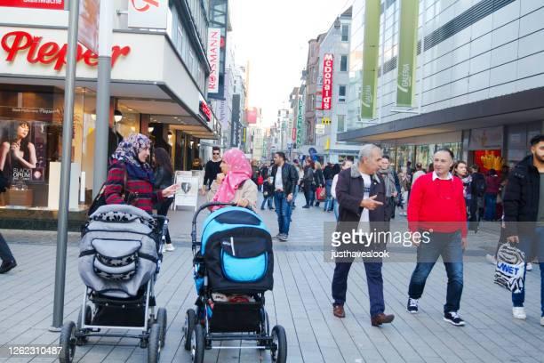 två unga muslimska kvinnor med barnvagnar och många fotgängare i dortmund - dortmund stad bildbanksfoton och bilder
