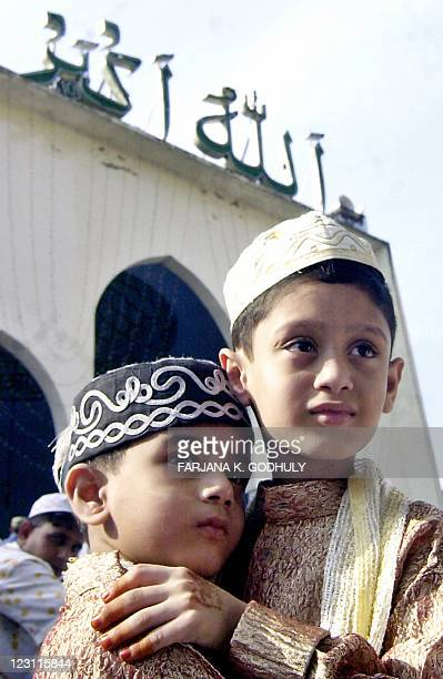 Two young Muslims greet each other after the special morning prayer with his father at Baitul Mukarram National Mosque in Dhaka 25 October 2006 to...